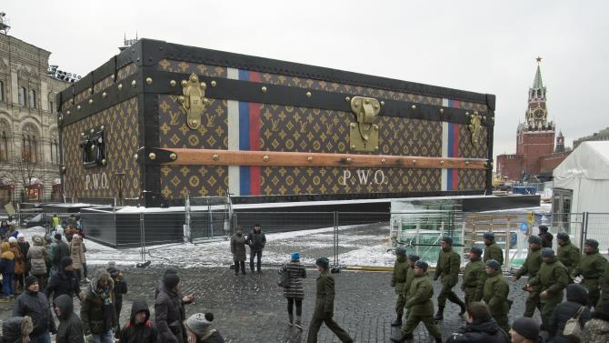 Tourists and visitors pass by a two-story Louis Vuitton suitcase erected at the Red Square in Moscow, Russia, Wednesday, Nov. 27, 2013. Politicians didn't like it, the public didn't like it, so the gigantic Louis Vuitton suitcase is being booted out of Red Square. The GUM department store on Red Square, which is responsible for 30-feet (nine meters) high and 100-feet (30-meters) long construction, promised in a statement released Wednesday that it would be dismantled. The GUM is at left and the Kremlin at right. (AP Photo/Pavel Golovkin)
