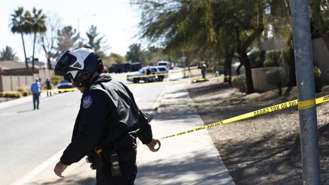 A Phoenix Police Department officer, puts up police tape near a home of a suspected gunman who opened fire at a Phoenix office building on, wounding three people, one of them critically, and setting off a manhunt that led police to surround his house for several hours before they discovered he wasn't there, Wednesday, Jan. 30, 2013, in Phoenix. Authorities believe there was only one shooter, but have not identified him or a possible motive for the shooting. They don't believe the midmorning shooting at the complex was a random act. (AP Photo/Ross D. Franklin)