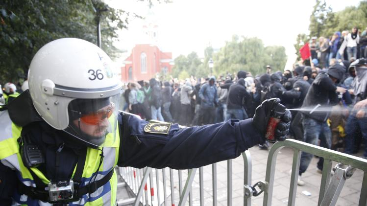 A police officer uses a spray during clashes with demonstrators protesting against an election meeting organised by right-wing political group Svenskarnas Parti, in Stockholm