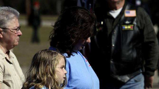 """Lauren Higginson, one of  Charles """"Chuck"""" Poland's bus riders, walks in with her mom to join friends and family gather to pay respects for Poland at the Ozark Civic Center on Sunday, Feb. 3, 2013, in Ozark, Ala. Authorities say Jim Lee Dykes, 65 — a decorated veteran of the Vietnam War known as Jimmy to neighbors — gunned down Poland, a school bus driver, and then abducted a 5-year-old boy from the bus, taking him to an underground bunker on his rural property. (AP Photo/Butch Dill)"""