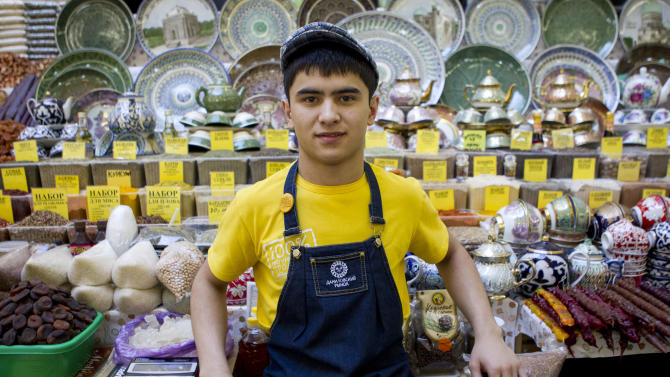 In this Aug. 22, 2012, photo Tajikistan native Magomed, 18, poses for a photo at a market stand where he sells spices, fruit and ceramics in Moscow. The old Moscow is rapidly giving way to a multi-ethnic city where Muslims from Central Asia are the fastest growing sector of the population. (AP Photo/Misha Japaridze)