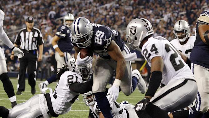 Dallas Cowboys running back DeMarco Murray (29) scores a touchdown in front of Oakland Raiders free safety Charles Woodson (24) during the second half of an NFL football game Thursday, Nov. 28, 2013, in Arlington, Texas. (AP Photo/The Waco Tribune-Herald, Jose Yau)