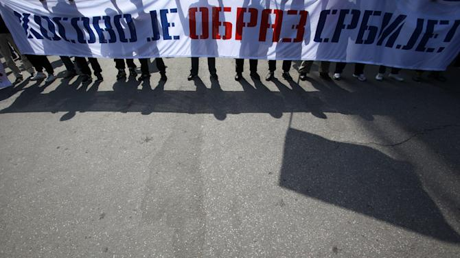 """Protesters carrying a banner that reads: """"Kosovo is Serbia's honor!"""" during the protest of Serbian nationalist organization Dveri, in Belgrade, Serbia, Sunday, April 21, 2013. Several hundred protesters gathered to protest against the recognition of Kosovo as an independent state. (AP Photo/Darko Vojinovic)"""