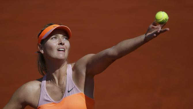 Maria Sharapova of Russia serves to Eugenie Bouchard of Canada during their women's semi-final match at the French Open tennis tournament at the Roland Garros stadium in Paris