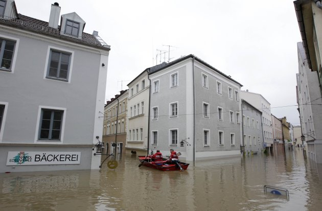 Members of the emergency services travel by boat along flooded streets in centre of Passau