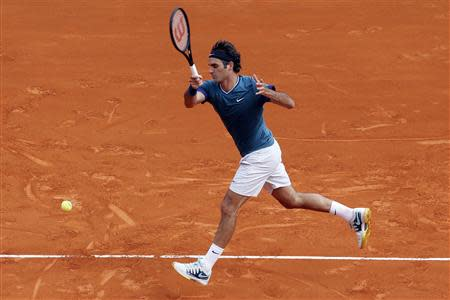 Federer of Switzerland returns the ball to Tsonga of France during their quarter-final match at the Monte Carlo Masters in Monaco