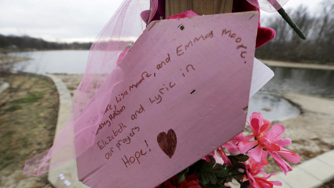 A sign sits attached to a memorial near Meyers Lake where cousins Lyric Cook, 10, and Elizabeth Collins, 8, disappeared in July while riding their bikes, Thursday, Dec. 6, 2012, in Evansdale, Iowa. Family members are waiting to hear whether the two bodies discovered by hunters on Wednesday are the two missing cousins. (AP Photo/Charlie Neibergall)