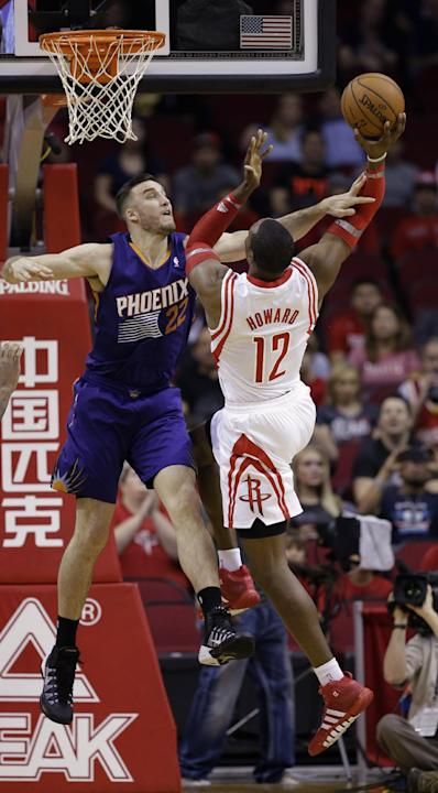 Houston Rockets' Dwight Howard (12) goes up for a shot as Phoenix Suns' Miles Plumlee (22) defends during the first quarter of an NBA basketball game Wednesday, Dec. 4, 2013, in Houston