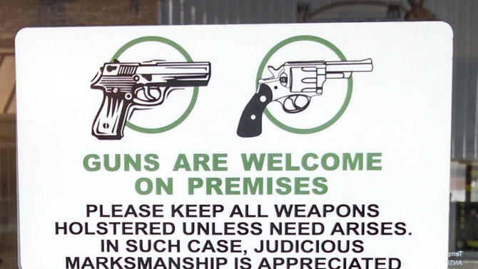 """A sign on the front door of Shooters Grill in Rifle, Colo., June 23, 2014, welcomes sidearms. A western Colorado restaurant doesn't just allow open gun carrying. Its waitresses carry loaded weapons right on their hips. At Shooters Grill in Rifle, open display of firearms is encouraged. A sign on the front door reads, """"Guns are welcome on premises. Please keep all weapons holstered, unless the need arises. In such cases, judicious marksmanship is appreciated."""" The restaurant also hosts concealed carry training that qualifies customers for Colorado and Utah permits. The $75 price tag includes dinner. (AP Photo/Glenwood Springs Post Independent, Christopher Mullen)"""