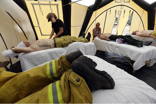 Several firefighters from Colorado Springs Fire Dept. get massages after coming off the fire line on the the Waldo Canyon wildfire west of Colorado Springs, Colo., Friday, June 29, 2012. One person has been found dead, another is missing and nearly 350 homes have been destroyed by a raging U.S. wildfire that has forced tens of thousands to flee this week. President Barack Obama on Friday will tour the scene of the most destructive fire in Colorado history.
