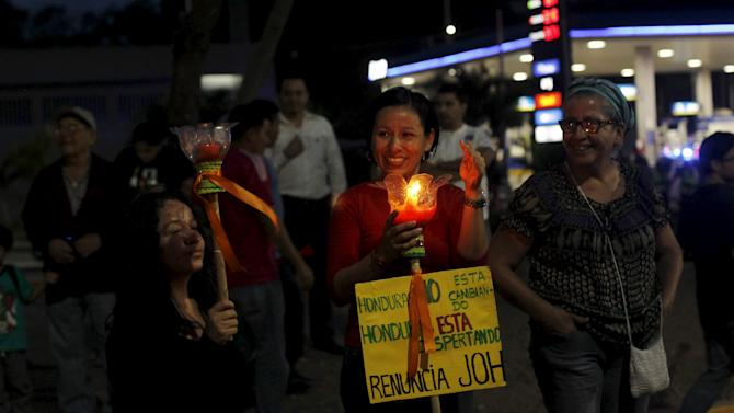 A woman holds a candle during a march to demand the resignation of Honduras' President Juan Hernandez in Tegucigalpa