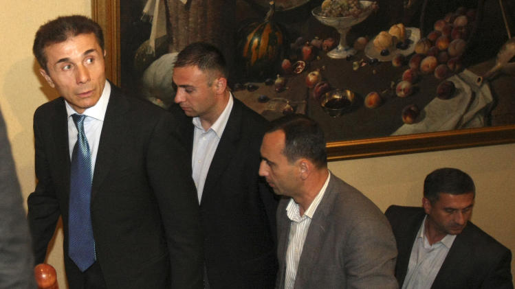 Georgia's billionaire and  the opposition Georgian Dream coalition leader Bidzina Ivanishvili, left, and his bodyguards walk for a meeting with Georgian businessmen in Tbilisi, Georgia on Friday, Oct. 5, 2012. The incoming government is likely to be headed by billionaire businessman Bidzina Ivanishvili, whose Georgian Dream coalition has according to preliminary figures secured more than 80 seats in the 150-member parliament. But the talks are taking place against the backdrop of opposition claims of vote-rigging it says have denied it a more commanding majority.(AP Photo/Shakh Aivazov)