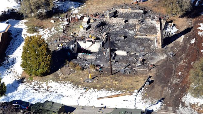 In this aerial photo, law enforcement authorities investigate the burn-out cabin Wednesday, Feb.13, 2013 where accused quadruple-murder suspect Christopher Dorner was believed to have died after barricading himself inside, during a Tuesday stand-off with police in the Angeles Oaks area of Big Bear, Calif. San Bernardino Sheriff's Deputy Jeremiah MacKay was killed and another wounded during the shootout with Dorner. (AP Photo/The Sun, John Valenzuela)