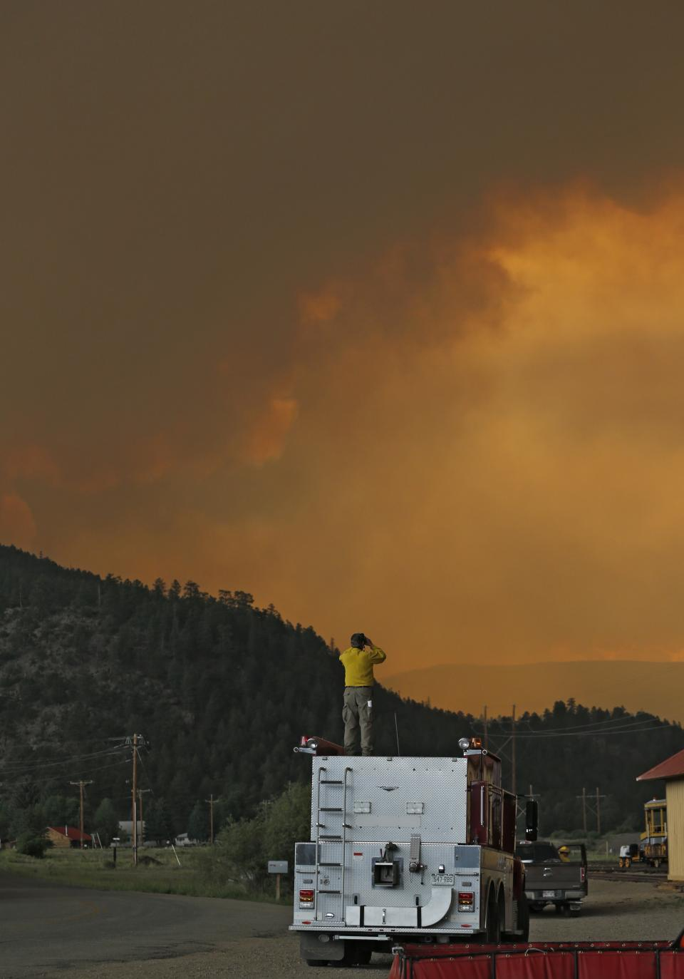 A firefighter stands on top of a fire truck in South Fork, Colo., as he monitors a wildfire that burns west of town on Friday evening June 21, 2013. The town was evacuated and U.S. 160 that passes through it was closed. (AP Photo/Ed Andrieski)