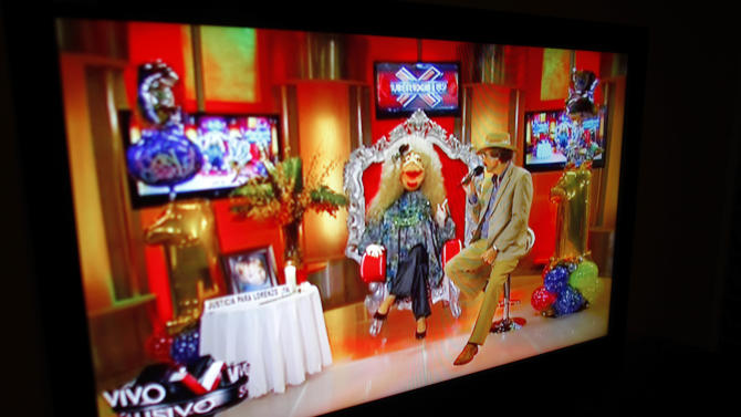 "FILE - In this Oct. 17, 2012 file photo, a TV show called ""La Comay,"" roughly translated to ""The Godmother"", is seen on a TV set in San Juan, Puerto Rico. This five-foot tall puppet with red lips, a shrill voice and a penchant for salacious details rules Puerto Rico's gossip circuit, with legions tuning into her show every afternoon ready for the latest bombshell. Joe Ramos, president of WAPA TV, told reporters late Thursday, Dec. 20, 2012 that the SuperXclusivo show will be taped two hours before it is broadcast. The announcement follows a recent outcry over comments that the controversial puppet made about a man who was brutally killed. (AP Photo/Ricardo Arduengo, File)"