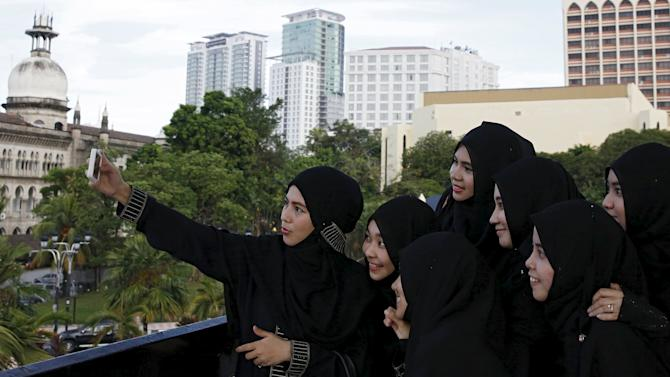 Women pose for a picture at the national mosque during Ramadan in Kuala Lumpur