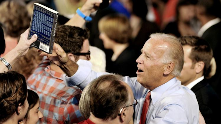 "Vice President Joe Biden greets supporters as one hands him a copy of the book ""Joe Biden"" after he addressed a grassroots rally, Tuesday, Aug. 21, 2012, in Minneapolis. (AP Photo/Jim Mone)"