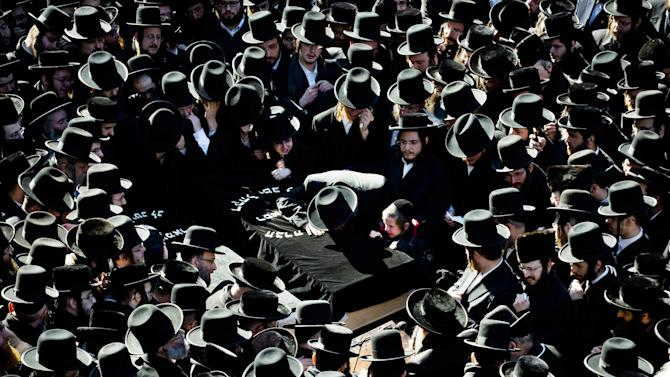 FILE  -  In this file photo of March 3, 2013, mourners surround a casket outside the Congregation Yetev Lev D'Satmar synagogue at the funeral for two expectant parents who were killed in a car accident early Sunday, in the Brooklyn borough of New York. The baby of Nachman and Raizy Glauber, a boy, was delivered prematurely cesarean section and survived until the next morning but died around 5:30 a.m. on Monday, March 4, 2013. Police were searching for the driver of a BMW and a passenger who fled on foot after slamming into the livery cab that transporting the 21-year-old couple to a hospital. (AP Photo/John Minchillo, File)