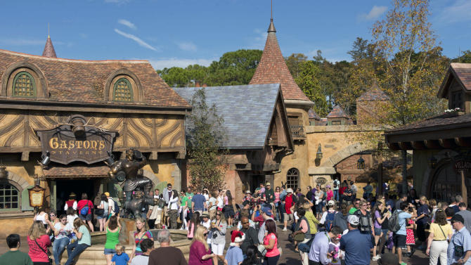 """This image released by Disney shows people outside of Gaston's Tavern, inspired by Disney's animated film """"Beauty and the Beast,"""" following the grand opening of New Fantasyland at Walt Disney World Resort in Lake Buena Vista, Fla. New Fantasyland, the largest expansion project in the park's 41-year history which doubled the size of the original Fantasyland, features attractions, dining, shopping, and character interactions. (AP Photo/Disney, David Roark)"""