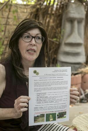 Laura Whitney shows a warning letter from the city …