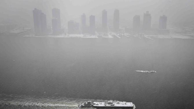 A tug boat pushes a barge down the East River as pictured from the United Nations building as it snows in the Manhattan borough of New York