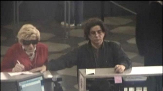 This May 2009 photo from video provided by the Brooklyn District Attorney's office shows, according to prosecutors, Thomas Parkin, 49, at left, on a Department of Motor Vehicles security camera, dressed up as his mother, who died in 2003, as part of a scam to collect her government benefits. At right is Mhilton Rimolo, a friend of Parkin's who authorities say acted as an accomplice in the scheme, posing as the mother's nephew when going to cash checks and do other business, prosecutors said. Parkin was convicted May 3, 2012 on charges including grand larceny and mortgage fraud. He was sentenced to 13 2/3 to 41 years, Monday May 21, 2012. (AP Photo/Brooklyn District Attorney's office)