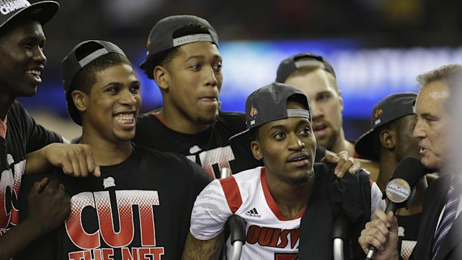 Louisville players and Louisville guard Kevin Ware  (5) celebrate their team's win over Michigan 82-76 after the NCAA Final Four tournament college basketball championship game Tuesday, April 9, 2013, in Atlanta. (AP Photo/Charlie Neibergall)
