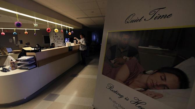 """In this Friday, June 8, 2012 photo, a sign is posted for """"quiet time"""" while a nurse works under dimmed lighting at the Newborn Family Unit at the Massachusetts General Hospital in Boston. Anyone who's had a hospital stay knows the beeping monitors, the pagers and phones, the hallway chatter, the roommate, even the squeaky laundry carts all make for a not-so-restful place to heal.  Hospitals need a prescription for quiet, and new research suggests it may not be easy to tamp down all the noise for a good night's sleep.  (AP Photo/Elise Amendola)"""