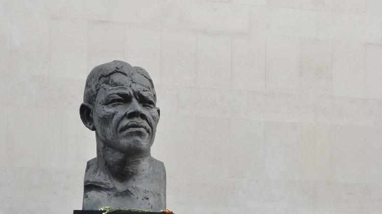 Passers-by look at a statue of former South African President Nelson Mandela on the South Bank in central London