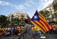 """A man with a pro-independence Catalan flag walks in front of people forming a human chain to mark the """"Diada de Catalunya"""" (Catalunya's National Day) in central Barcelona September 11, 2013. REUTERS/Albert Gea"""