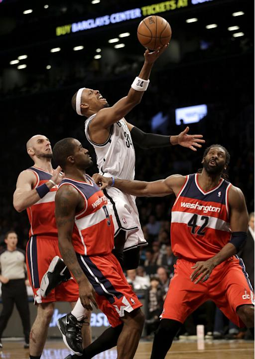 Brooklyn Nets' Paul Pierce, top, scores over Washington Wizards' Marcin Gortat, left, Nene Hilario, right, and Martell Webster during the second half of an NBA basketball game Wednesday, Dec.