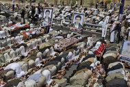 Anti-government protestors and relatives of tribesmen, loyal to Sheik Sadeq al-Ahmar, the head of the powerful Hashid tribe, who were killed recently in clashes with Yemeni security forces, pray around their bodies during their funeral procession in Sanaa, Yemen, Friday, June 10, 2011. Nearly 100,000 Yemenis are protesting in a main square of the capital demanding the wounded president, currently outside the country, be removed from power. (AP Photo/Hani Mohammed)