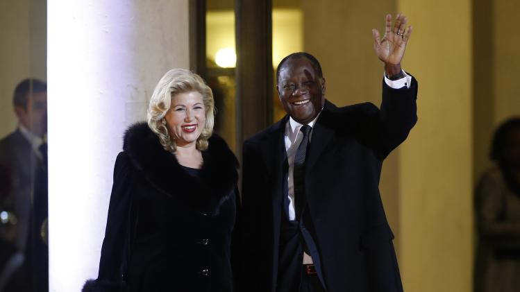 Ivory Coast's president Alassane Ouattara and first lady Dominique Ouattara arrive for a dinner with the French President and other dignitaries as part of the Summit for Peace and Security in Africa at the Elysee Palace in Paris