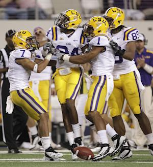 LSU's Tyrann Mathieu (7), Tharold Simon (24), Eric Reid (1) and Lavar Edwards (89) celebrate an interception by Simon against Oregon in the first half of the Cowboys Classic NCAA college football game Saturday, Sept. 3, 2011, in Arlington, Texas. (AP Photo/Tony Gutierrez)