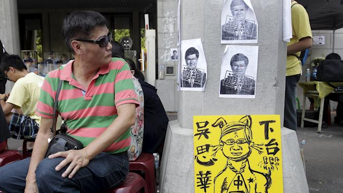 An activist looks at the papers with Taiwan's Education Minister Wu Se-hwa's picture during a protest at the entrance to the Ministry of Education in Taipei