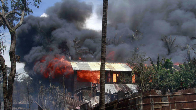 Smokes and flames billow from burning buildings in Sittwe, capital of Rakhine state in western Myanmar, where sectarian violence is ongoing Tuesday, June 12, 2012. Gunshots rang out and residents fled blazing homes in western Myanmar on Tuesday as security forces struggled to contain deadly ethnic and religious violence that has killed at least a dozen people and forced thousands to flee. (AP Photo/Khin Maung Win)