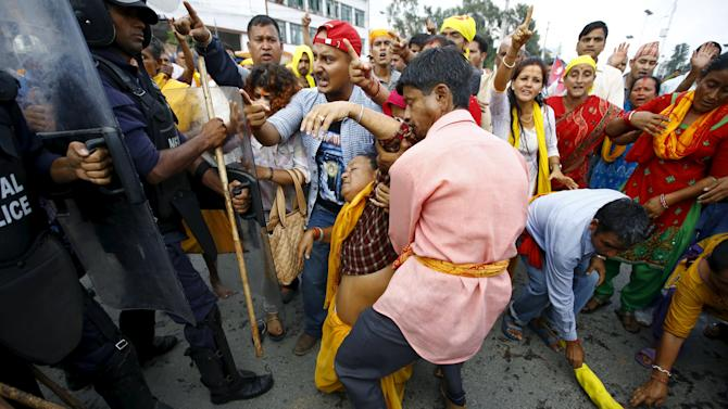 A Hindu activist faints after falling down during a clash in Kathmandu