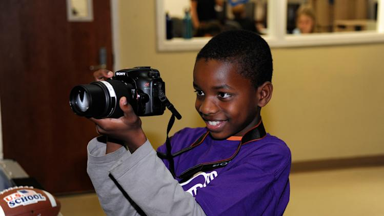 IMAGE DISTRIBUTED FOR BOYS & GIRLS CLUBS OF AMERICA - In this image released on Monday, Jan. 7, 2013, a boy from Boys & Girls Clubs of San Dieguito takes a photograph during an event with Sony Electronics in San Diego. The event kicked off a national partnership between Boys & Girls Clubs of America and Sony, which seeks to engage Club youth nationwide to explore and build their skills in photography, digital arts and self-expression.  The San Diego Club event included photography workshops for youth using the latest Sony camera technology taught by Sony volunteers. It also featured a special visit by renowned photographer and Sony Artisan of Imagery, Matthew Jordan Smith, known for photographing top names in the entertainment industry. (Denis Poroy/ AP Images for Boys & Girls Clubs of America )
