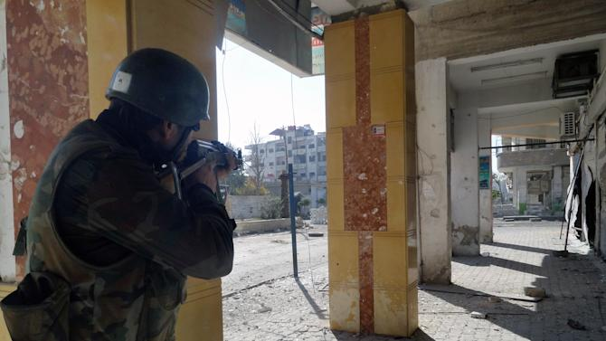 In this Sunday, Dec. 2, 2012 photo released by the Syrian official news agency SANA, a Syrian soldier aims his rifle at free Syrian Army fighters during clashes in the Damascus suburb of Daraya, Syria. Syrian warplanes and artillery pummeled areas in and around Damascus, Aleppo and several other cities, on Sunday according to reports received by human rights activists. Intense fighting persists as rebels try to push their way back into the capital, where President Bashar Assad has his power base. (AP Photo/SANA)