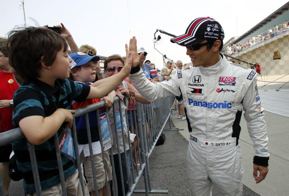 IndyCar driver Takuma Sato, of Japan, greets fans on the final day of practice for the Indianapolis 500 auto race at the Indianapolis Motor Speedway in Indianapolis, Friday, May 25, 2012. The 96th running of the race is Sunday. (AP Photo/Tom Strattman)