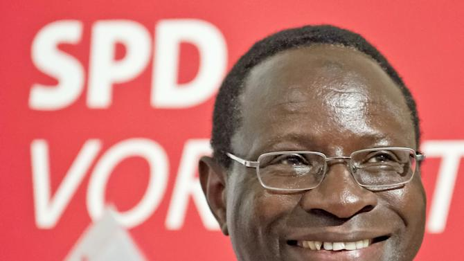 In this picture taken July 25, 2013, Karamba Diaby, a German Social Democratic Party candidate, smiles during an election campaign in Halle , central Germany, Thursday, July 25, 2013. He was born in Senegal and moved to the former GDR to study at the University of Leipzig. Diaby, now 51, is campaigning for a Bundestag seat to become the country's first black member of Parliament. (AP Photo/Jens Meyer)