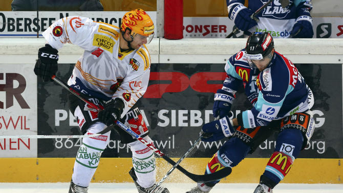 In this photo made available Sunday, Dec. 10, 2012 Bern' s NHL lockout player John Tavares from the New York Islanders, left, challenges for the puck with Rapperswil's Antonio Rizzello, right, during the Swiss first league hockey match between Rapperswil-Jona Lakers and SC Bern, in Rapperswil, Switzerland, Saturday, Dec. 8, 2012. (AP Photo/Keystone, Thomas Oswald)