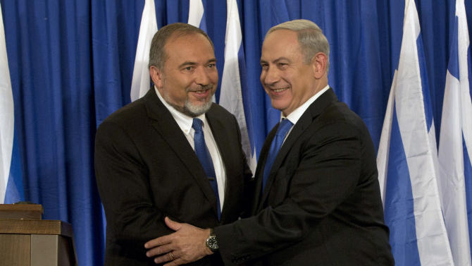 Israeli Prime Minister Benjamin Netanyahu, right, and  Foreign Minister Avigdor Lieberman shake hands in front the media after giving a statement in Jerusalem, Thursday, Oct. 25, 2012. Netanyahu said his Likud Party will join forces with the hard-line party of his Foreign Minister in upcoming parliamentary elections. (AP Photo/Bernat Armangue)