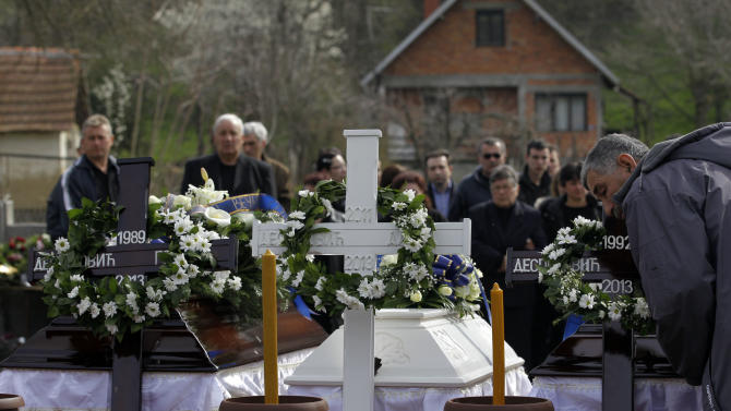 A man pays his last respects in front of coffins containing bodies of victims of a shooting prior to a mass funeral in the village of Velika Ivanca, some 50 kilometers (30 miles) southeast of Belgrade, Serbia, Friday, April 12, 2013. The village of Velika Ivanca is preparing for the funerals of thirteen victims of a shooting that happened on Tuesday, April 9, 2013. Ljubisa Bogdanovic, a local and a Yugoslav wars veteran, went from house to house on April 9 in the village at dawn, cold-bloodedly gunning down his mother, his son, a 2-year-old cousin and ten other neighbors. (AP Photo/ Darko Vojinovic)