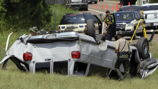 Emergency workers work at the scene where a church van crashed on an exit off Interstate 40 near Waverly, Tenn., on Thursday, July 28, 2011. One person was killed and at least three children were seriously injured. (AP Photo/Mark Humphrey)