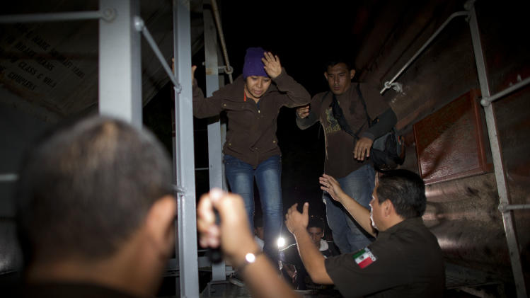 RESENDING RLB101 TO REPLACE CORRUPT FILE - Immigration officials remove Central American migrants from a northbound freight train during a raid by federal police in San Ramon, Mexico, just after midnight on the morning of Friday, Aug. 29, 2014. The largest crackdown by Mexican authorities on illegal migration in decades has decreased the flow of Central American migrants trying to reach the United States, and has dramatically cut the number of child migrants and families, according to officials and eyewitness accounts along the perilous route. (AP Photo/Rebecca Blackwell)