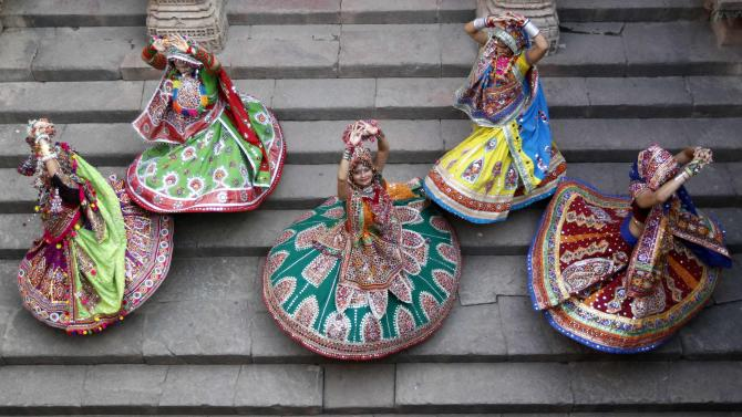 "Women dressed in traditional attire pose as they take part in rehearsals for the ""garba"" dance ahead of Navratri festival at Adalaj Stepwell Ahmedabad"