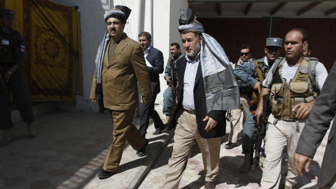 Afghan Defense Minister Besmillah Khan Mohammadi, center, and Afghan Interior Minister Mujtaba Patang, left, walk in Gushta district of Jalalabad, east of Kabul, Afghanistan, Monday, Oct, 1, 2012. Afghan Defense and Interior Ministers held a meeting with locals in Gushta district of Nangarhar about recent rocket attacks from Pakistan. (AP Photo/Rahmat Gul)