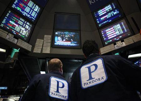 Traders work at the kiosk where Pandora internet radio is traded on the floor of the New York Stock Exchange