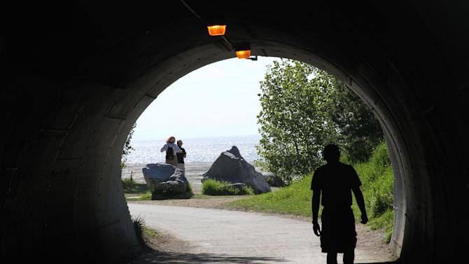 This photo taken June 11, 2013, shows a man running in a tunnel along the Tony Knowles Coastal Trail in downtown, Anchorage, Alaska, while others admire Cook Inlet. Anchorage offers more than 135 miles of multi-use trails in the city. (AP Photo/Mark Thiessen)